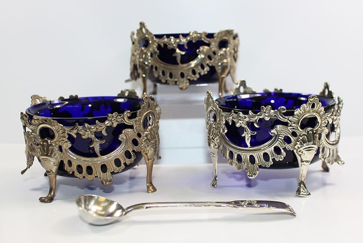 Three blue glass and silver salt cellars with silver spoon in front.