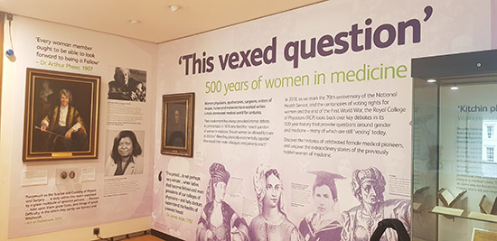 Photograph of part of the exhibition 'This vexed question' including text and reproductions on walls, and photographic and painted portraits of women.