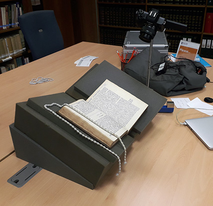 An old book on foam supports, with a camera on a tripod above it.