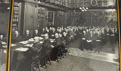 Black and white photograph of a large meeting in a wood-panelled library