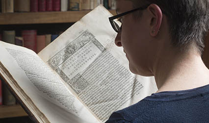 Photograph of a woman looking at a book