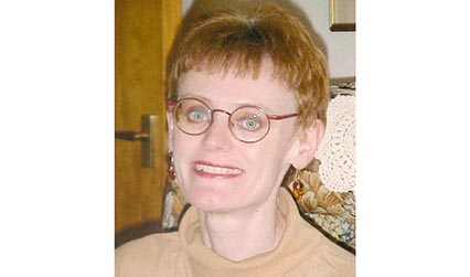 Photograph of a woman with short auburn hair and glasses.