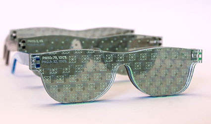 Photograph of three pairs of glasses made of transparent green material, with different symbols etched onto the surfaces of the lenses.