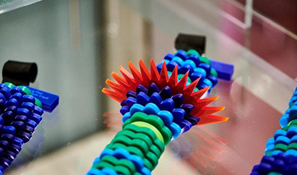Photograph of a necklace displayed on a glass shelf. The necklace is made from half-discs of plastic of different shapes and colours. Some are smooth and green, some are curved and blue, and one is spiky and red.
