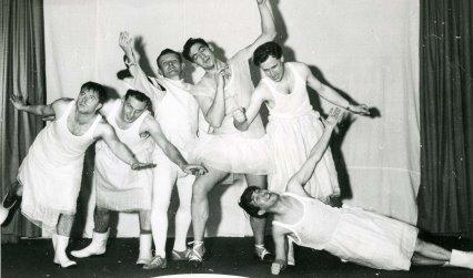 Black and white photograph of a group of men wearing white dresses performing on stage in a comedy show