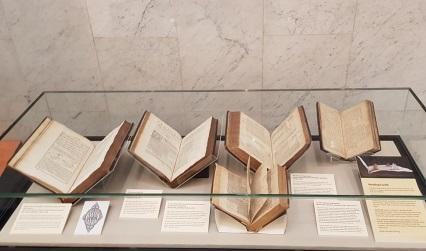 Photograph of early printed books on display in a glass case