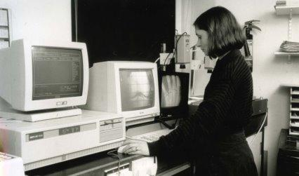Photograph of a women standing in front of a computer terminal