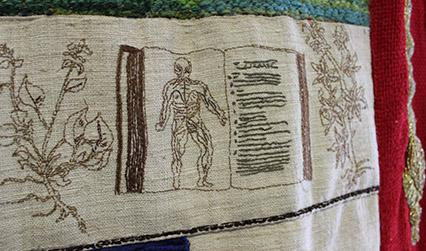 Photograph of an embroidered tapestry depicting pages from historical books about anatomy and medicinal plants.