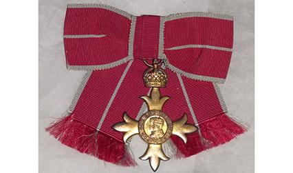 Colour photograph of a gold, cross-shaped medal with red ribbon