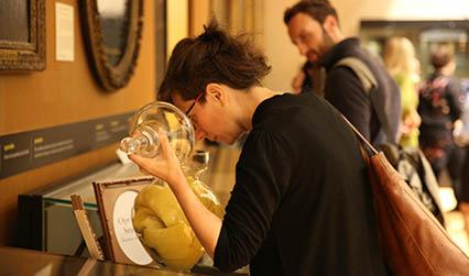 An exhibition visitor smelling a scented jar
