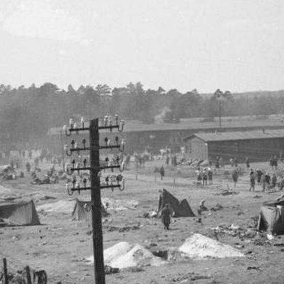 Black and white photograph of a prison camp and fence.