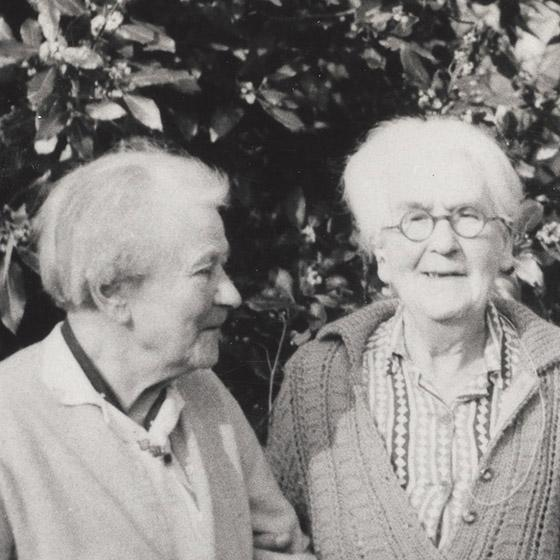 Black and white photograph of two eldery white women standing arm-in-arm in a garden.