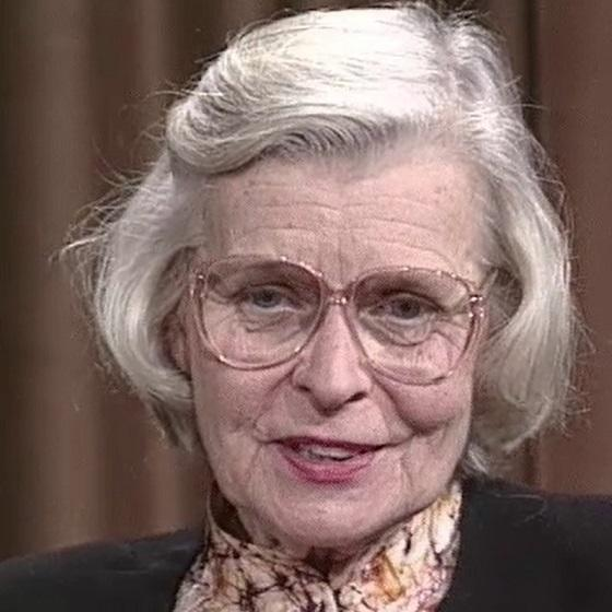 A white woman with white hair, wearing glasses.